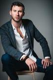 被射击的演播室时尚:英俊的年轻人画象牛仔裤、衬衣和夹克的坐长凳 免版税图库摄影