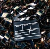 被展开的堆35mm电影filmstrip颜色地毯和clapperboard 免版税库存照片