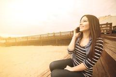 被应用的微笑的女孩谈的电话温暖的过滤器 免版税库存照片
