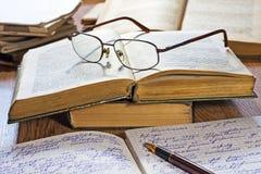 被开张的笔记本、笔、书和玻璃 免版税图库摄影
