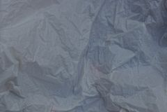 被弄皱的灰色玻璃纸片断的塑料纹理  库存图片