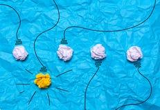 被弄皱的纸创造性的想法  在蓝色背景的一个灼烧的电灯泡 登记概念教育查出的老 库存图片