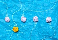 被弄皱的纸创造性的想法  在蓝色背景的一个灼烧的电灯泡 登记概念教育查出的老 免版税库存照片