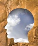 被弄皱的纸形状作为一个人头 在hea里面的多云天空 库存照片