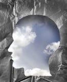 被弄皱的纸形状作为一个人头 在hea里面的多云天空 免版税库存图片