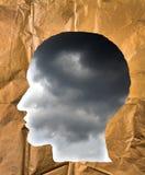 被弄皱的纸形状作为一个人头 在hea里面的风雨如磐的天空 免版税库存照片