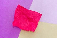 被弄皱的纸红色板料在几个颜色背景中:黄色,桃红色,紫色 库存照片