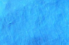 被弄皱的蓝色布料物质片段作为背景textur 免版税库存照片