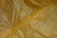 被弄皱的黄色玻璃纸片断的塑料纹理  图库摄影