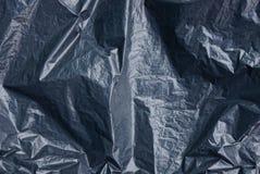 被弄皱的黑玻璃纸片断的塑料纹理  库存图片