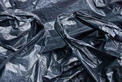 被弄皱的黑玻璃纸片断的塑料纹理  免版税图库摄影