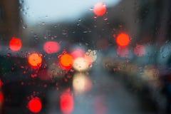 被弄脏的光通过一块湿挡风玻璃 免版税库存图片