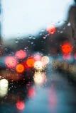 被弄脏的光通过一块湿挡风玻璃 免版税库存照片