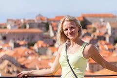 被弄脏的全景都市风景背景的美丽的年轻白肤金发的女孩  杜布罗夫尼克市 免版税库存图片