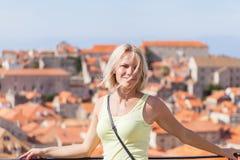被弄脏的全景都市风景背景的美丽的年轻白肤金发的女孩  杜布罗夫尼克市 库存图片