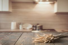 被弄脏的和抽象厨房背景 木桌面用麦子和显示的defocused现代厨房您的产品 免版税库存图片