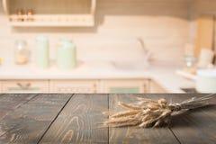 被弄脏的和抽象厨房背景 木桌面用麦子和显示的defocused现代厨房您的产品 图库摄影