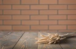被弄脏的和抽象样式 与麦子和defocused砖墙背景的耳朵的木桌面显示或蒙太奇的 免版税库存照片