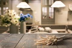 被弄脏的和抽象背景 与盘子的空的木桌面和显示或蒙太奇yo的defocused现代厨房背景 图库摄影