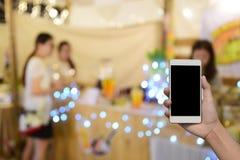 被弄脏的图象手举行和触摸屏聪明的电话和食物在 免版税库存照片