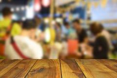 被弄脏的图象木桌和食物在夜节日与bokeh b 免版税库存图片