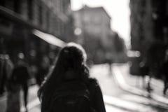 被弄脏的妇女从后面走穿过被弄脏的城市 免版税图库摄影