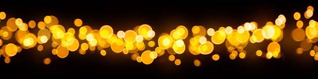 被弄脏的抽象金黄斑点在黑背景点燃 库存照片
