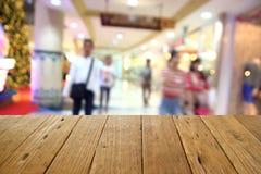 被弄脏的木桌和商城中心和人backgroun 免版税库存照片