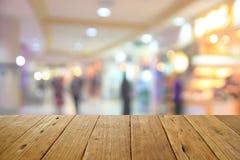 被弄脏的木桌和商城中心和人backgroun 图库摄影