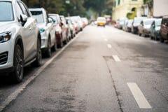 被弄脏的汽车在都市街道边停放了 免版税库存照片
