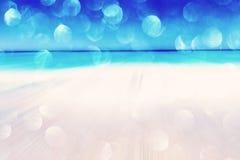 被弄脏的海滩和海背景挥动与bokeh光沙子 免版税库存图片