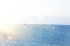 被弄脏的海滩和海背景挥动与bokeh光 免版税库存图片