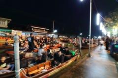被弄脏的焦点泰国人等待唱专题歌并且举在小船的蜡烛为陛下国王普密蓬・阿杜德祈祷 免版税库存照片