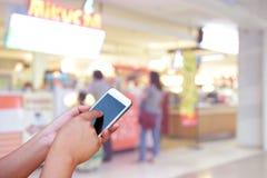 被弄脏的照片和智能手机在商城背景与bo 库存图片