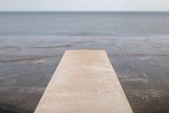 被弄脏的照片长的水泥桥梁延伸到有自然的海 图库摄影