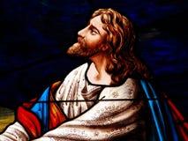 被弄脏的玻璃耶稣祈祷 图库摄影