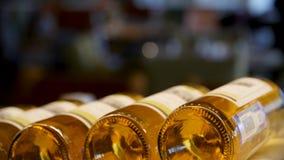 被弄脏的瓶白色和玫瑰酒红色在一个架子连续恰好被计划在一个大超级市场 抽象明亮 免版税库存图片