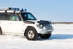 被弄脏的白色SUV行动,当快速地移动雪表面上时 库存照片