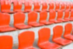 被弄脏的红色空的塑料体育场位子 库存图片
