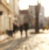 被弄脏的背景人民在老城市镇中心日落的 免版税库存图片