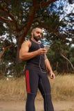 被弄脏的背景的一位肌肉运动员 听到一些音乐的一位嬉戏慢跑者在跑前 体育,音乐 图库摄影