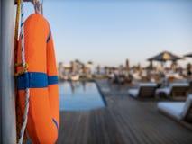 被弄脏的背景的橙色lifebuoy近的公开游泳场,游泳场是可看见的 免版税库存照片