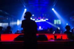 被弄脏的背景:棍打,迪斯科愉快的人民人群的DJ使用的和混合的音乐  夜生活,音乐会光 库存图片