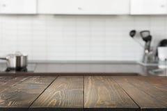 被弄脏的背景 有空的木桌面和空间的现代defocused淡色厨房 库存照片