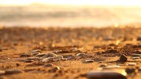被弄脏的自然本底海小卵石和被弄脏的波浪在日落 股票录像