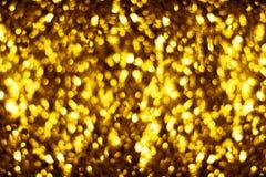 被弄脏的金黄发光的闪烁bokeh背景,defocused黄色淡光背景设计,金光亮的圆的泡影弄脏作用 免版税库存照片