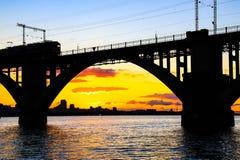 被成拱形的铁路桥和一列火车剪影在第聂伯河美好的日落的 第聂伯罗彼得罗夫斯克 库存照片