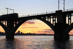 被成拱形的铁路桥和一列火车剪影在美好的日落 第聂伯河,Dnipo市,乌克兰 免版税库存照片