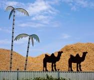 被截去的骆驼剪影和金属棕榈在锯木屑存贮市分 免版税库存照片
