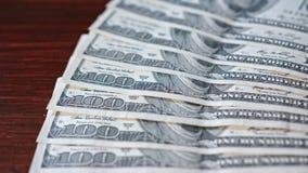 被扇动的堆在表上的一百美元钞票 免版税库存图片
